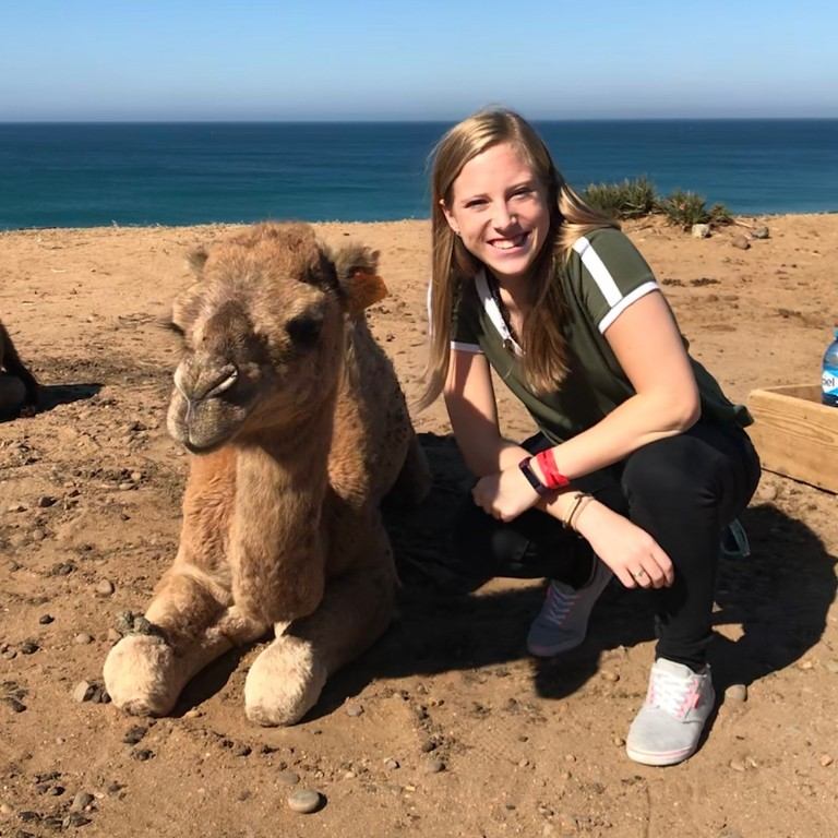 A student posing with a camel