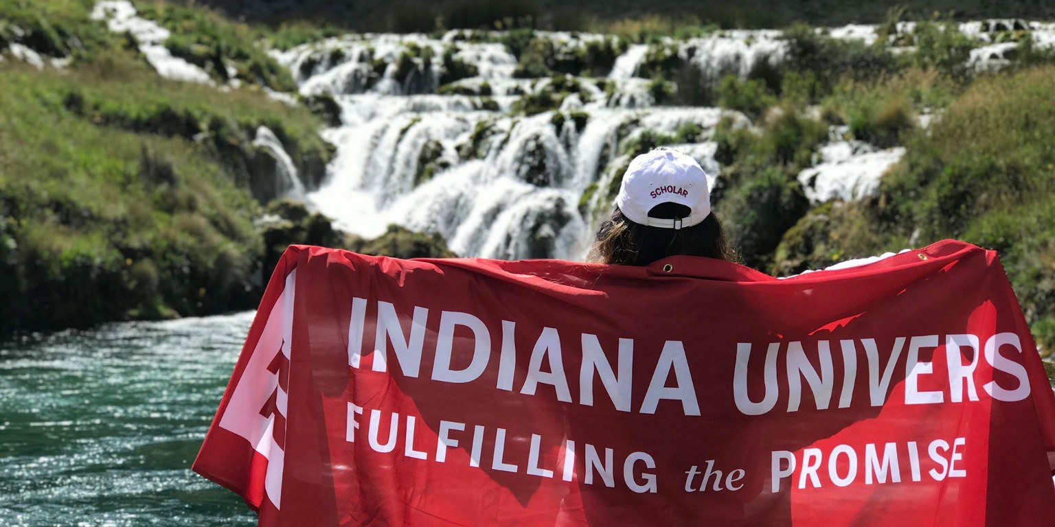 HIEP recipients in South America - Angela Perez holds an Indiana University flag while standing in front of a beautiful waterfall in Peru