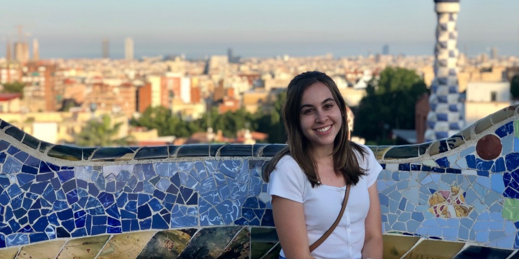 Jordan Zatz sits on a mosaic bench in Barcelona Spain with the city in the background.
