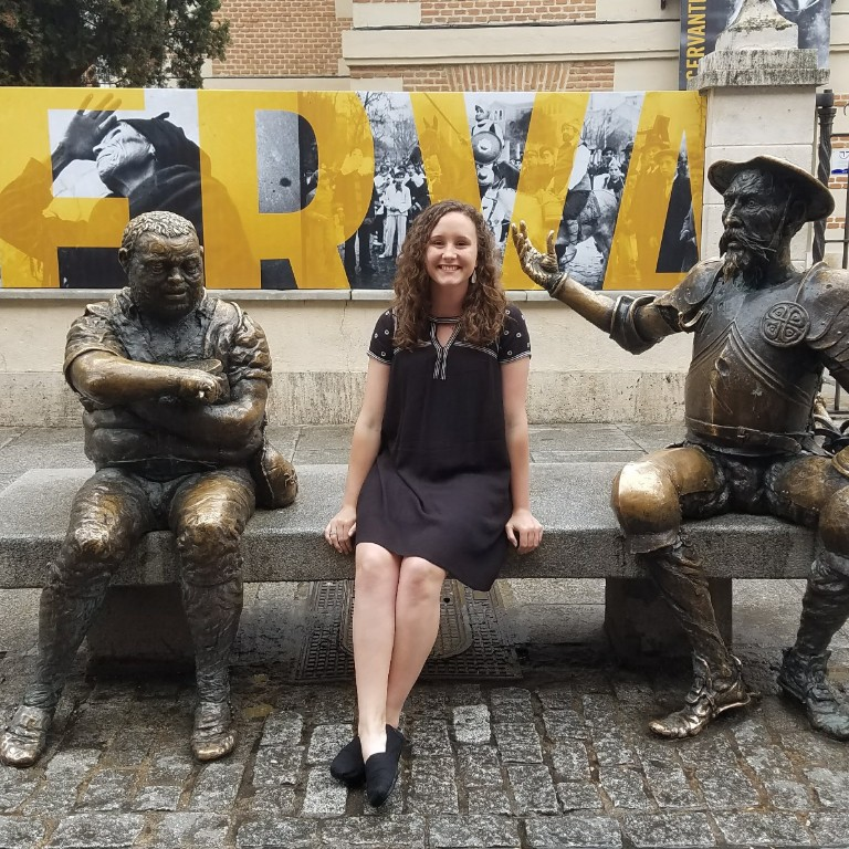 HIEP recipients in Spain - Amanda Tolen sits on a bench in Alcala Spain with statues on either side