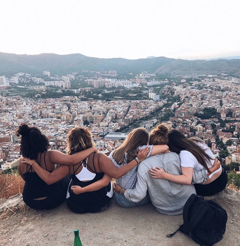 HIEP recipients in Spain - Dannie Henton and 3 friends embrace each other while looking out over Barcelona from an overlook