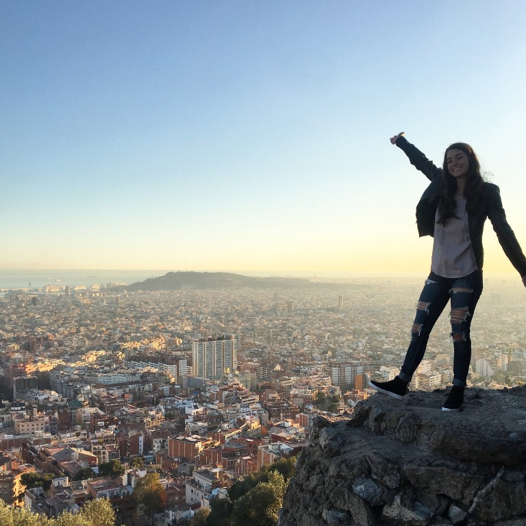 HIEP recipients in Spain - Madison Cavanaugh poses on a rock outcrop overlooking a beautiful view of Barcelona
