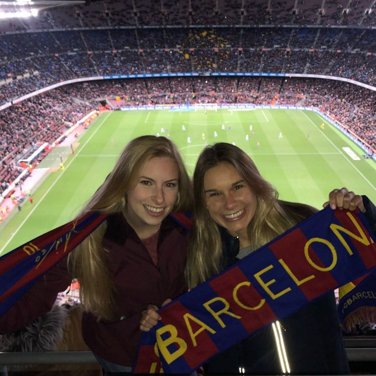 HIEP recipients in Spain - Natalie Pitts and a friend wave a Barcelona flag at a soccer game in a filled arena in Barcelona