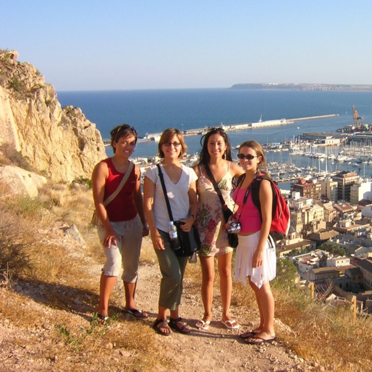 Sarah Overpeck and friends in Spain with a beach and town in the background.