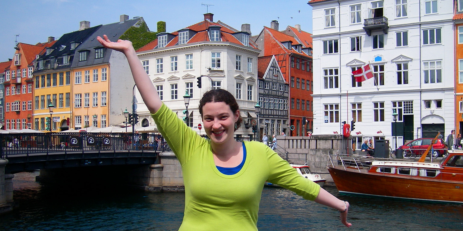 A student posing for a photo in front of a canal in Copenhagen with a row of colorful buildings in the background