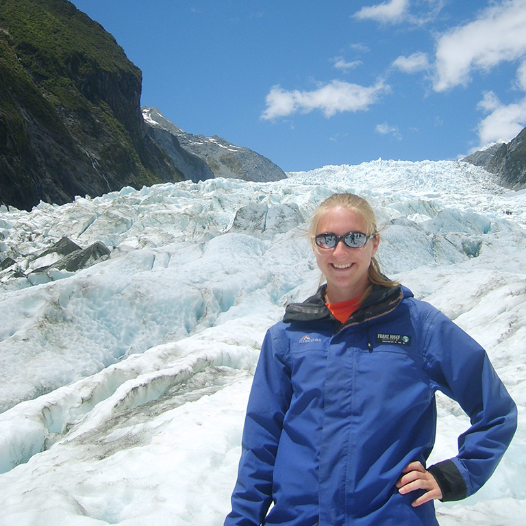Student posing for a photo in front of a large glacier