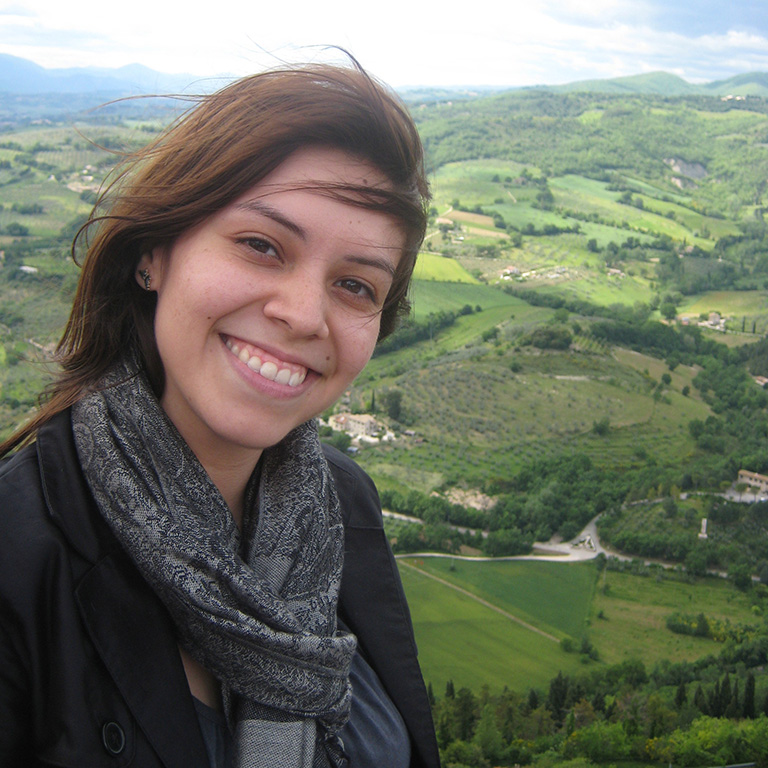 Student smiling for a photo at a location overlooking rolling hills and green pastures